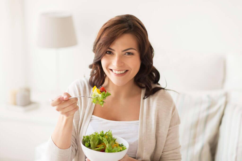 smiling young woman eating salad at home